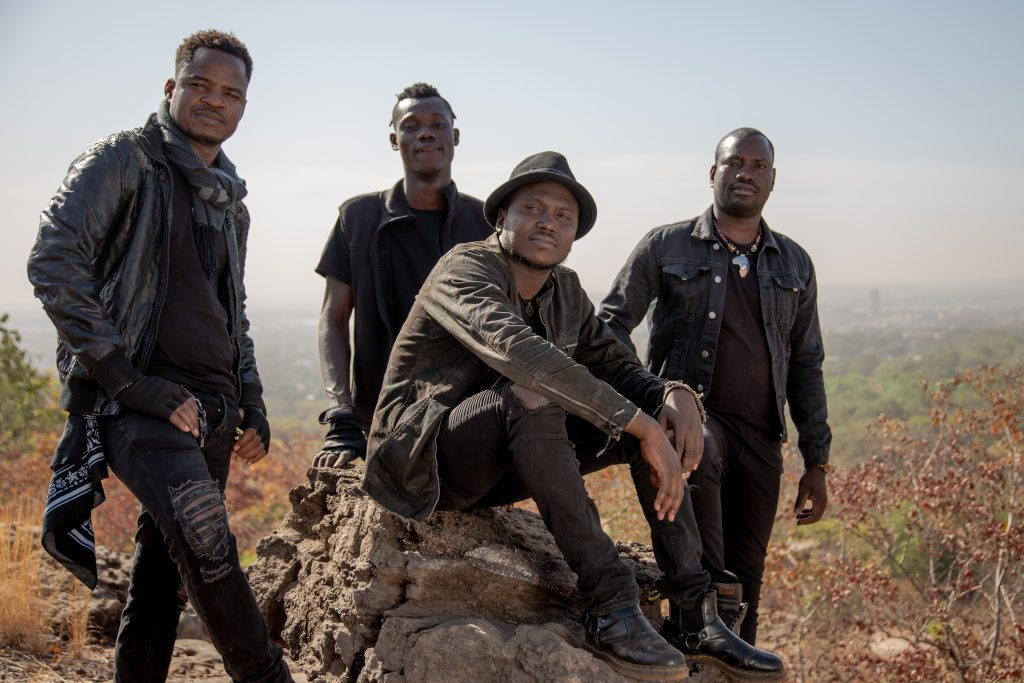 The band dressed in dark clothing with Aliou sitting on a rock surrounded by the other members