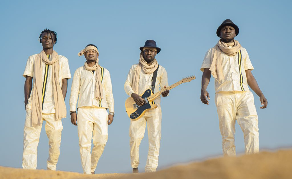 The four band members dressed in white walking towards you in a desert setting